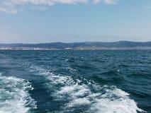 Fond de vague d'été de surface de la Mer Noire Vue de yacht Paysage marin exotique avec les nuages et la ville sur l'horizon Tran photographie stock libre de droits