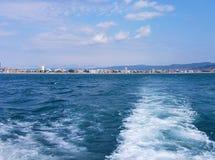 Fond de vague d'été de surface de la Mer Noire Vue de yacht Paysage marin exotique avec les nuages et la ville sur l'horizon Tran image stock