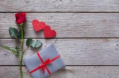 Fond de Valentine avec la fleur de rose de rouge, les coeurs de papier et la boîte actuelle sur le bois rustique Images stock