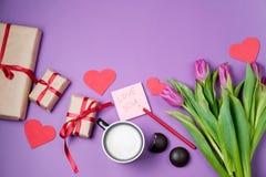 Fond de Valentine avec le boîte-cadeau, le bonbon, les coeurs et les tulipes dessus Images libres de droits