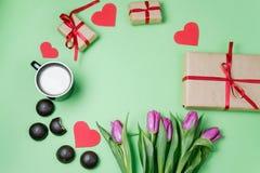 Fond de Valentine avec le boîte-cadeau, le bonbon, les coeurs et les tulipes dessus Photos libres de droits