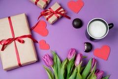 Fond de Valentine avec le boîte-cadeau, le bonbon, les coeurs et les tulipes dessus Photographie stock libre de droits