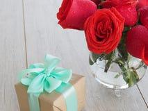Fond de Valentine de boîte-cadeau avec le ruban et l'arc et groupe de roses rouges sur le bois L'espace pour la copie Photographie stock