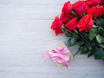 Fond de Valentine de boîte-cadeau avec le ruban et l'arc et groupe de roses rouges sur le bois L'espace pour la copie Photos libres de droits