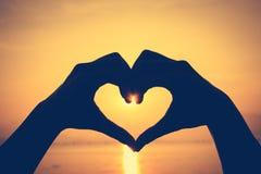 Fond de Valentine Silhouette de main de forme d'amour sur le backgrou de ciel Image stock
