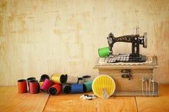 Fond de vintage avec les outils de couture et kit de couture au-dessus de fond texturisé en bois Photos stock
