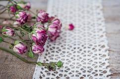 Fond de vintage avec les roses de thé sèches sur la dentelle et la toile de jute Photos libres de droits
