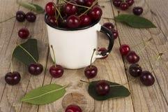 Fond des cerises mûres Pile des cerises fraîches et savoureuses dans la tasse emal Photos stock