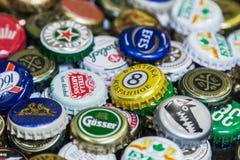 Fond des chapeaux de bouteille à bière, un mélange de diverses marques globales Photographie stock libre de droits