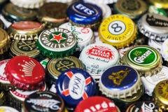 Fond des chapeaux de bouteille à bière, un mélange de diverses marques globales Images libres de droits