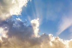 Fond des nuages colorés, du soleil derrière les nuages et des rayons de soleil dans le ciel Images stock