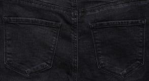 Fond des poches arrières de jeans noirs photos stock