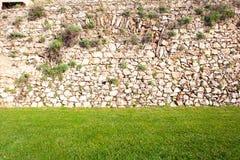 Fond du mur en pierre avec l'herbe Photo libre de droits