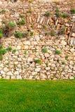 Fond du mur en pierre avec l'herbe verte Images libres de droits