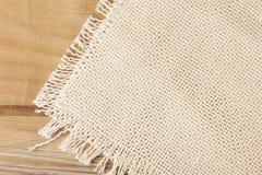 Fond du tissu de toile brut blanc sur un conseil en bois images stock