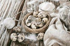 Fond en bois avec des oeufs de caille dans un nid de paille, serviette de cuisine Image stock