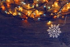 Fond en bois avec la guirlande et un flocon de neige Fond pendant Noël et l'année neuve Photo libre de droits