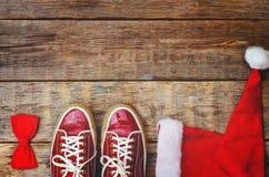Fond en bois avec le capot rouge d'espadrilles et un arc Photographie stock