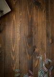 Fond en bois avec le carnet et les trombones colorés Photographie stock libre de droits