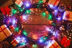Fond en bois avec les lumières et les étoiles colorées entouré par des cadeaux et des cônes Photographie stock