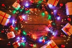 Fond en bois avec les lumières et les étoiles colorées entouré par des cadeaux et des cônes Photo stock