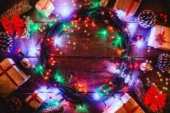 Fond en bois avec les lumières et les étoiles colorées entouré par des cadeaux et des cônes Images libres de droits