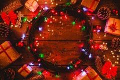 Fond en bois avec les lumières et les étoiles colorées entouré par des cadeaux et des cônes Image libre de droits