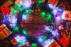 Fond en bois avec les lumières et les étoiles colorées entouré par des cadeaux et des cônes Photos stock
