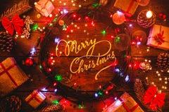 Fond en bois avec les lumières et les étoiles colorées entouré par des cadeaux et des cônes avec le message de centre de Joyeux N Photo libre de droits