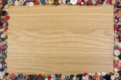 Fond en bois avec une frontière colorée de bouton Images stock