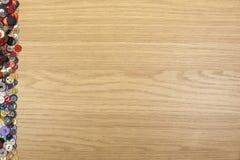 Fond en bois avec une frontière colorée de côté gauche de bouton Photographie stock libre de droits
