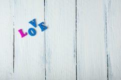 Fond en bois blanc avec l'amour de mot dans les lettres en bois Photographie stock