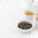 Fond en bois blanc avec la théière et les tasses de thé vert Image stock