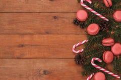 Fond en bois de Brown avec des branches de sapin, de macaron, et de bâtons de caramel Photo libre de droits