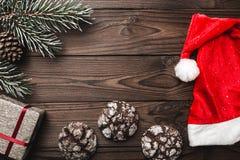 Fond en bois de Brown Carte de voeux Chapeau du ` s de Santa Arbre de sapin, cône décoratif bonbons L'espace de message pendant N photo stock
