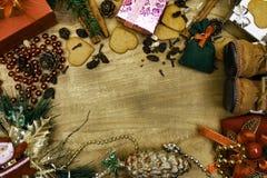 Fond en bois de Noël, bottes de Santa, pains d'épice, raisins secs, gingembre, cardamome, clous de girofle, cadeaux décoratifs de photographie stock libre de droits
