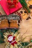 Fond en bois de Noël, bottes de Santa, pains d'épice, raisins secs, gingembre, cardamome, clous de girofle, cadeaux décoratifs de photo stock