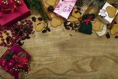 Fond en bois de Noël Pains d'épice de Noël, raisins secs, gingembre, cardamome, clous de girofle, cadeaux décoratifs de pain d'ép images stock
