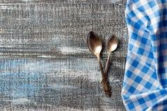 Fond en bois de table avec les couverts et la nappe pliée à carreaux bleue photographie stock libre de droits