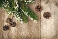 Fond en bois de vintage de Noël avec des branches et des cônes de sapin Photographie stock libre de droits