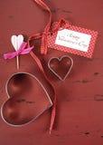 Fond en bois de vintage rouge de jour de valentines avec des coupeurs de biscuit de forme de coeur Photos stock