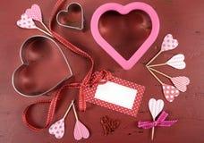Fond en bois de vintage rouge de jour de valentines avec des coupeurs de biscuit de forme de coeur Photo libre de droits