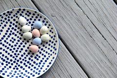 Fond en bois gris avec le plat modelé tenant des oeufs de pâques de sucrerie Photo stock