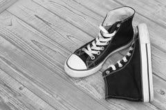 Fond en bois grunge noir et blanc monochrome avec des espadrilles de toile de vintage Photos libres de droits