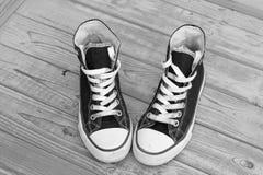 Fond en bois grunge noir et blanc monochrome avec des espadrilles de toile de vintage Image libre de droits
