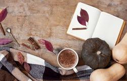 Fond en bois rural avec le potiron et les feuilles d'automne, une tasse de latte de potiron avec du café ou cacao, un carnet, un  image stock