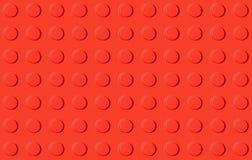 Fond en plastique rouge de jouet de construction Photographie stock libre de droits