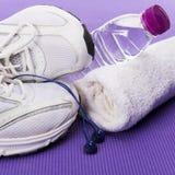 Fond, espadrilles, écouteurs, bouteille d'eau et serviette de forme physique Image stock