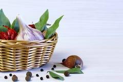 Fond et épices La feuille de laurier dans un panier en osier, ail a photo stock