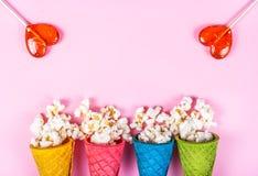 Fond et bonbons roses Maïs éclaté et lucettes clairsemés Copiez l'espace Maïs éclaté dans un cône de gaufre Photo stock